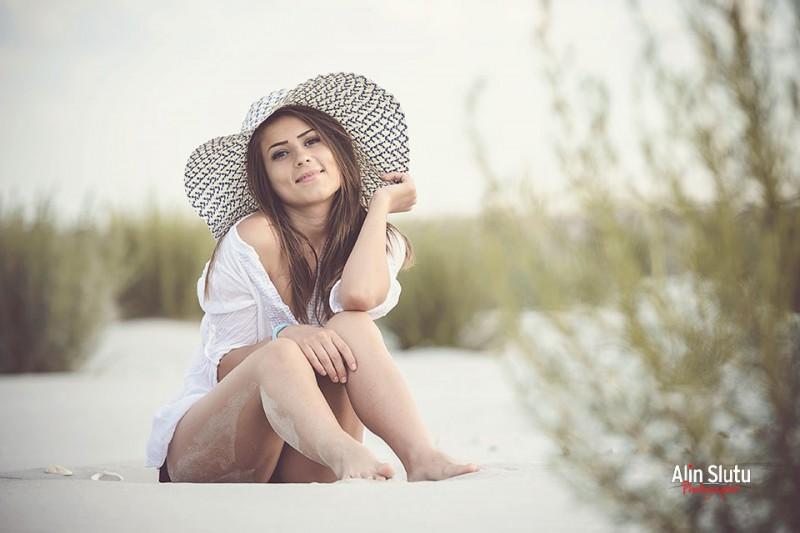 fotografie fata cu palarie pe plaja